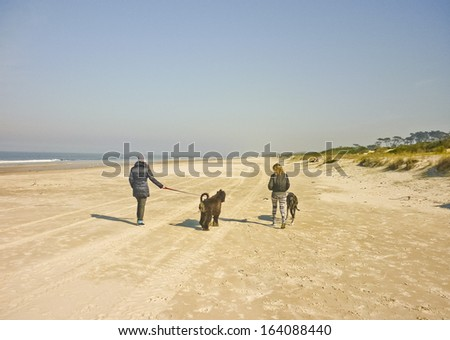 Two girls walking with his big pets on a deserted beach in a sunny day in winter. - stock photo