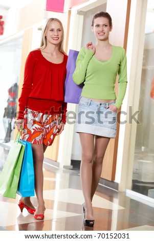 Two girls walking with shopping bags - stock photo