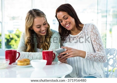 two girls watch a phone while eating and drinking - stock photo