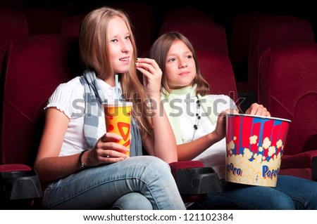 Two girls watching a movie at the cinema - stock photo