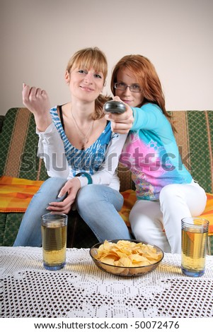 Two girls watching TV in living room, with two juice and some snack on table. Concept of entertainment, TV, friendship, relaxing