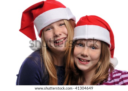 Two girls wearing Christmas hats and smiling isolated on a white background