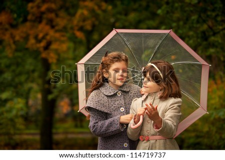 Two girls wearing coats  and felt hats  in autumn park  looking retro style