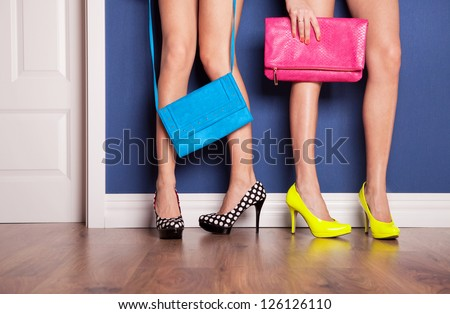 Two girls wearing high heels waiting at the door - stock photo