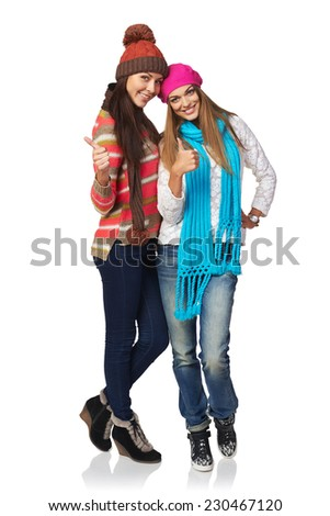 Two girls wearing winter clothing in full length, white background - stock photo