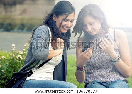 Two Girls While Speaking Looking the cell phone