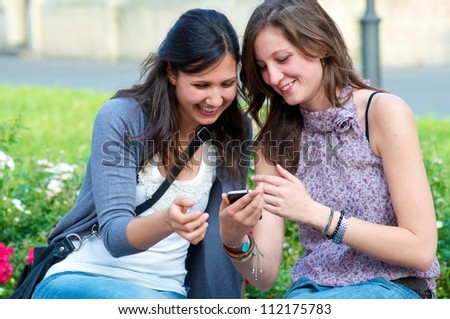 Two Girls while They speak At the Cellular