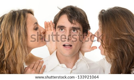 Two girls whispering in the ears of a young man - stock photo