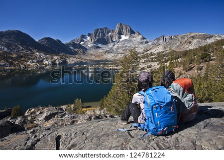 Two girls with backpacks sitting on top of hill,  looking at a lake Thousand islands lakes, Eastern Sierra, California - stock photo