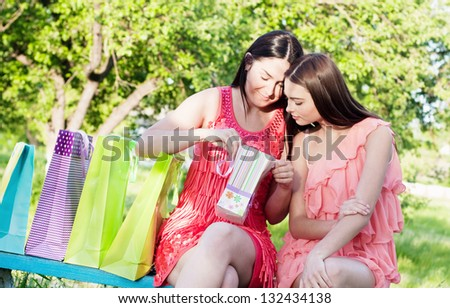 two girls with colored bags outdoor - stock photo