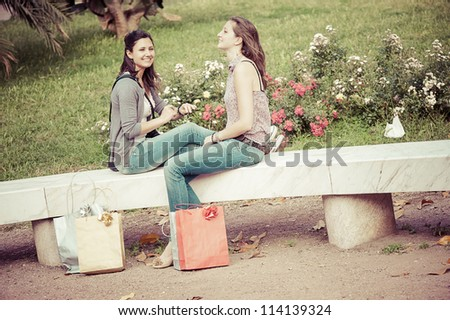 two girls with colored bags outdoor,italy - stock photo