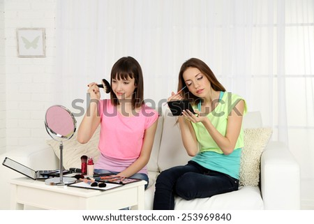 Two girls  with decorative cosmetics on home interior background - stock photo