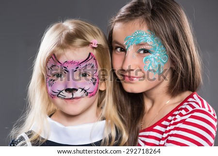 Two girls with painted faces posing indoors - stock photo
