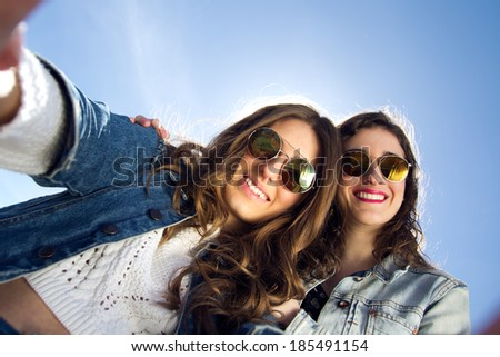 Two girls with sunglasses taking photos with a smartphone - stock photo