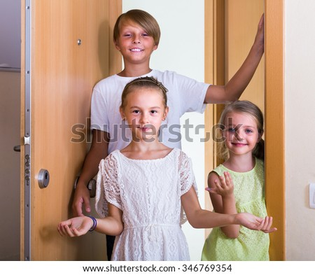 Two girls with teenage boy meeting in doorway and laughing - stock photo