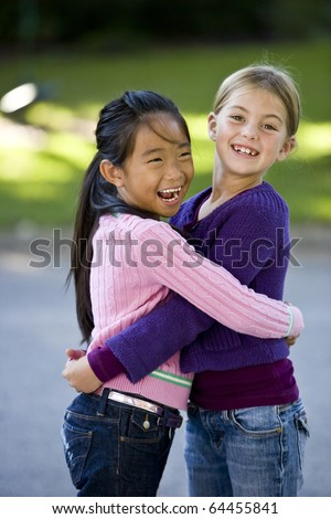 Two girls, 7 years, happy together - stock photo