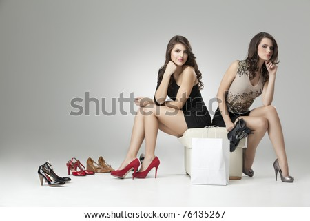 two glamorous women red gray high heels
