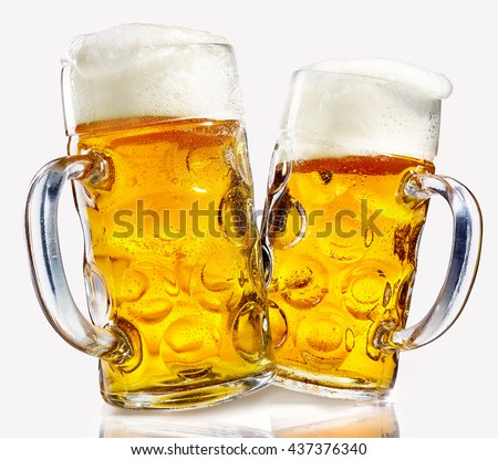 two glass beer mugs full of golden lager with thick frothy heads over a reflective white