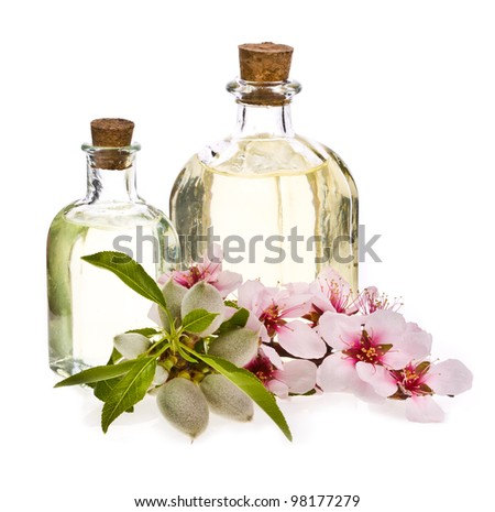 Two glass bottles filled with almond oil and fresh almonds and flowers isolated on the white background