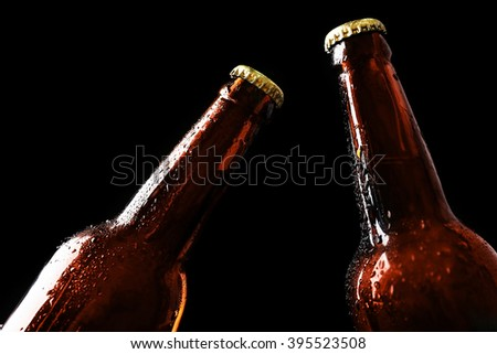 Two glass bottles of beer on black background - stock photo