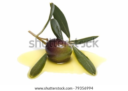 Two glass bottles of virgin olive oil and some black olives isolated on a white background.