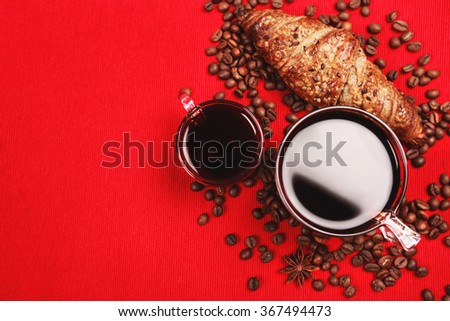 Two glass cups of black coffee for breakfast with croissant and coffee beans lying on red textile background
