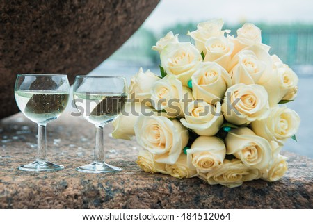 Two glass flutes with champagne and a beautiful wedding bouquet of white roses.