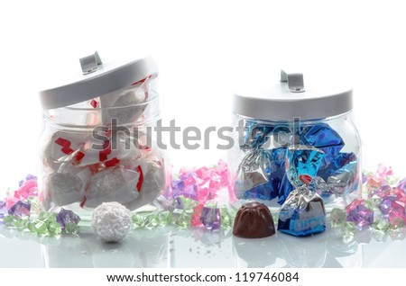 Two glass jars of luxury foil wrapped Christmas chocolates with delicious unwrapped examples displayed in the foreground for your festive greeting card - stock photo