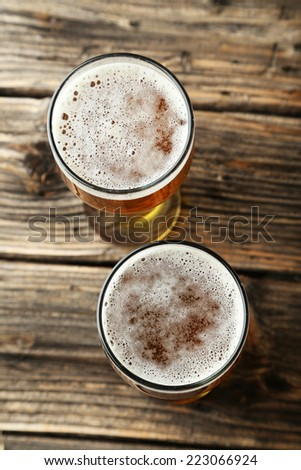 Two glass of beer on brown wooden background - stock photo