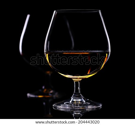 two glass of brandy on the black  - stock photo