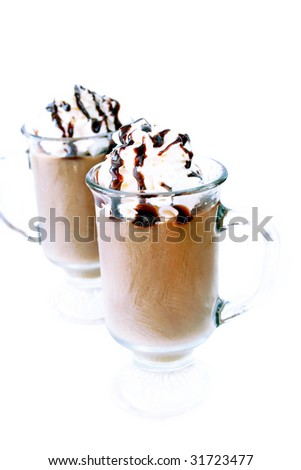 Two glass of coffee latte with whipped cream and chocolate syrup on a white background.