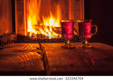 Two glass of hot drink on wooden background near the fireplace - stock photo