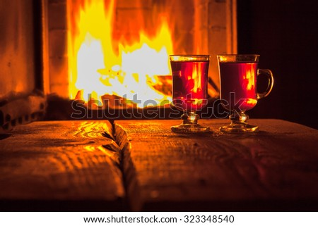 Two glass of hot drink on wooden background near the fireplace, selective focus, copyspace  - stock photo