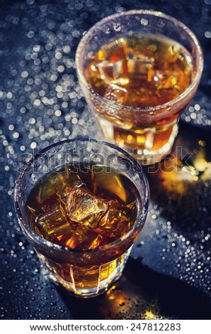 Two glass of iced cocktail on wet background