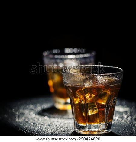 Two glass of iced cocktail on wet background. Shallow depth of field. - stock photo