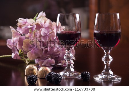 two glass of wine with chocolate and hydrangea flower - stock photo