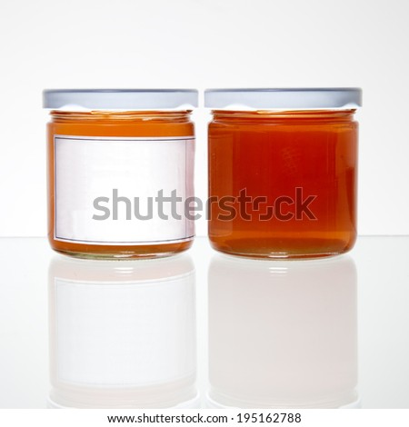 Two glass orange jelly jars against a white background, one with label, one without a label with slight reflection. - stock photo