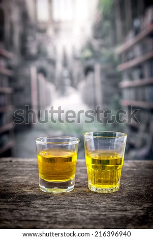 Two glass shots with yellow liqour resembling whiskey, rum, tequila, spirit on wooden table - stock photo