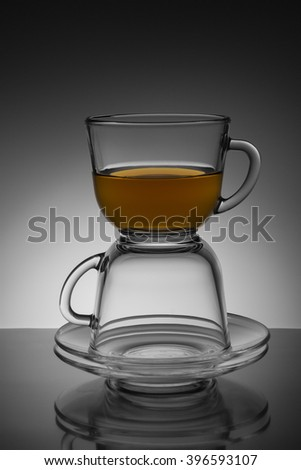 Two glass transparent cup with tea and saucer on a black and white background