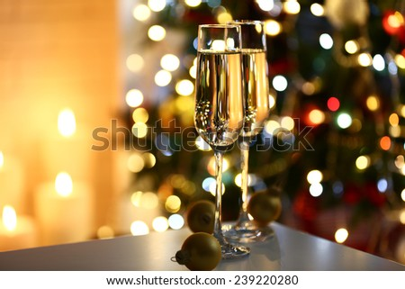 Two glass with champagne with chocolates and baubles on table on Christmas tree and fireplace background - stock photo