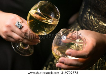 two glass with white wine, in a hands, in an interior