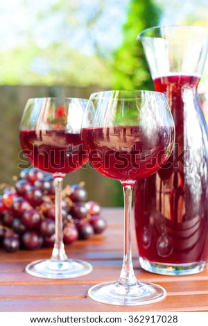 Two glasses and carafe of delicious homemade red wine with grape on wooden table. Multicolored summertime outdoors vertical image.