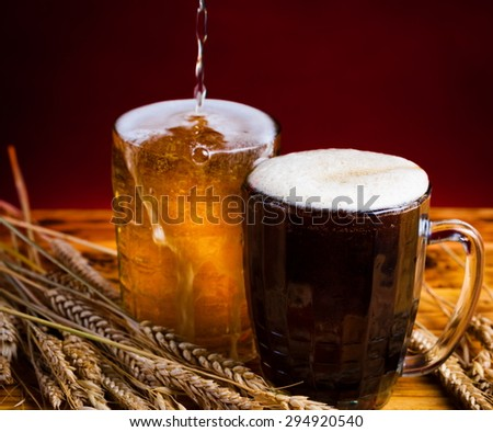 two glasses brown golden beer golden red background holiday Valentine Day event luxury life drink night ale foam wooden table pint russian kvass brew - stock photo