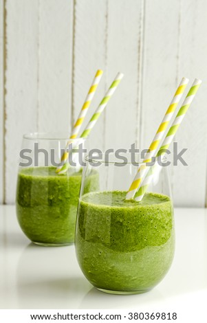 Two glasses filled with spinach and kale green detox smoothie with yellow and green swirled straws - stock photo