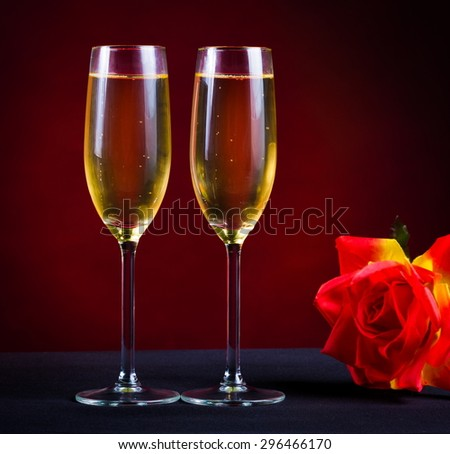 two glasses flutes golden champagne red background holiday Christmas new Year Valentine Day event luxury life drink night flower rose card gift - stock photo
