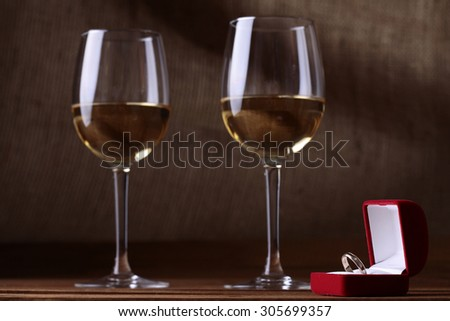 Two glasses full of white wine standing on brown wooden table top near small red velvet box with engagement golden ring on burlap background, horizontal picture