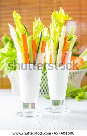 Two glasses of assorted fresh vegetables carrot, celery cucumber with yogurt dip on white wooden background, selective focus - stock photo