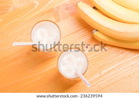 two glasses of banana juice on the table next to a yellow ripe bananas - stock photo