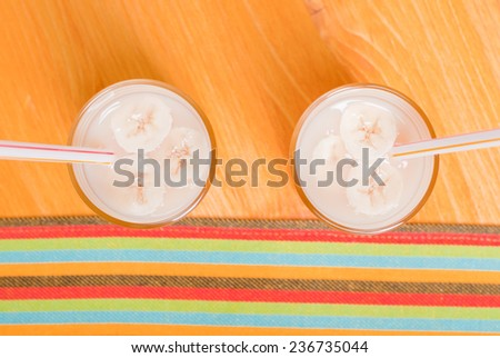two glasses of banana juice with slices of banana with tubes on a yellow table top view - stock photo