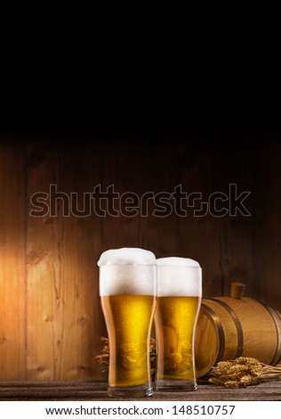 two glasses of beer, barrel and rye on wooden table. wooden background